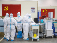 This photo taken on February 17, 2020 shows medical staff members working at an exhibition centre converted into a hospital in Wuhan in China's central Hubei province. - The death toll from the COVID-19 coronavirus epidemic jumped to 1,868 in China on February 18 after 98 more people died, according …
