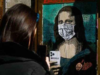 "A woman takes a picture with her mobile phone of a poster by Italian urban artist Salvatore Benintende aka ""TVBOY"" depecting Leonardo da Vinci's Mona Lisa wearing a protective facemask and holding a mobile phone reading ""Mobile World Virus"" in a street of Barcelona on February 18, 2020, a week …"