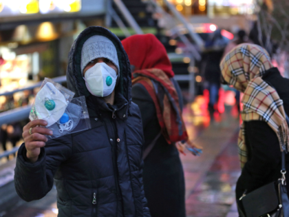 An Iranian street vendor sells protective masks in the capital Tehran on February 20,2020. - Two people have died in Iran yesterday after testing positive for the new coronavirus, the health ministry said, in the Islamic republic's first cases of the disease. (Photo by ATTA KENARE / AFP) (Photo by …