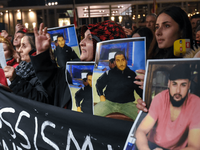 Mourners hold up photos, believed to be of vicitims, during a vigil close to a crime scene in Hanau, near Frankfurt am Main, western Germany, on February 20, 2020, after at least nine people were killed in two shootings late on February 19, 2020. - The suspect in two shootings …