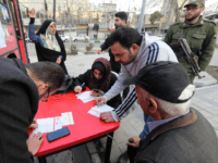 An Iranian man registers to vote at a mobile polling station in the capital Tehran on February 21, 2020. - Electoral authorities in Iran extended voting for two hours in the Islamic republic's parliamentary election on Friday, state television reported. (Photo by ATTA KENARE / AFP) (Photo by ATTA KENARE/AFP …