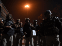 Police guard a street in an area following clashes between supporters and opponents of a new citizenship law in New Delhi on February 25, 2020. - Ten people were killed and more than 130 injured in some of the worst sectarian violence in India's capital in years, as rioters went …