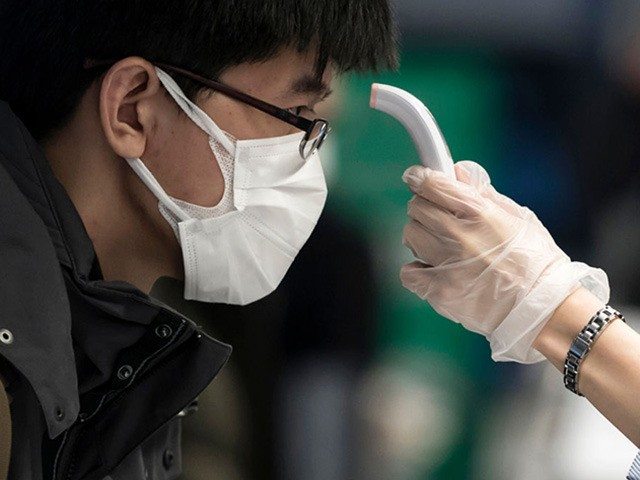 TOKYO, JAPAN - JANUARY 31: A passenger receives a temperature check before taking a flight bound for Wuhan at Spring Airlines' check-in counter at Haneda airport on January 31, 2020 in Tokyo, Japan. The Chinese government arranged a charter flight operated by Spring Airlines for tourists from Wuhan to return …