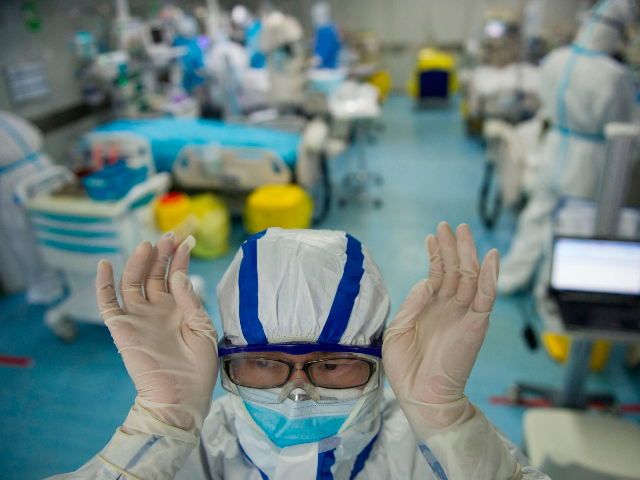 This photo taken on February 22, 2020 shows a nurse adjusting his goggles in an intensive care unit treating COVID-19 coronavirus patients at a hospital in Wuhan, in China's central Hubei province. - China on February 26 reported 52 new coronavirus deaths, the lowest figure in more than three weeks, …