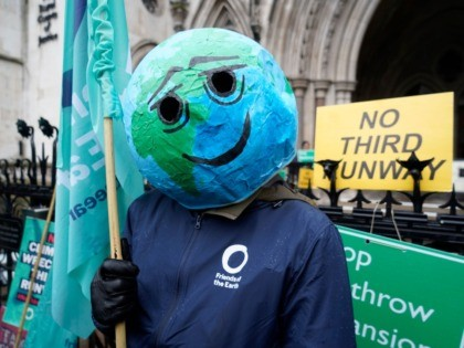 A campaigner wearing a papier-mache globe on his head is seen outside the Royal Courts of Justice in London on February 27, 2020 after a decision by the Court of Appeal on legal challenges to the UK government's approval of plans to expand capacity at Heathrow airport. - Britain's Court …