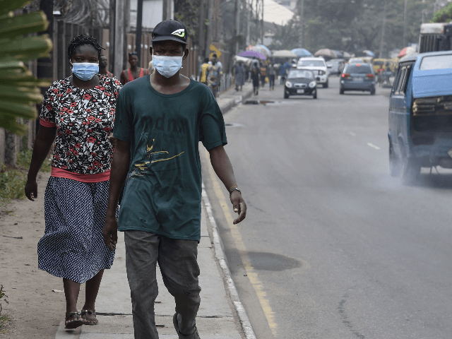 People walk along a main road wearing face masks at Yaba in Lagos, on February 28, 2020. - Residents of Nigeria's economic hub Lagos scrambled for hygiene products after the chaotic megacity of 20 million announced the first confirmed case of new coronavirus in sub-Saharan Africa. Health Minister Osagie Ehanire …