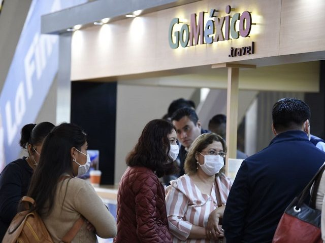 Passengers wearing protective masks are seen at the International Airport in Mexico City, on February 28, 2020. - Mexico's Health Ministry confirmed the country's first case of coronavirus on Friday, saying a young man had tested positive for it in the capital. (Photo by ALFREDO ESTRELLA / AFP)