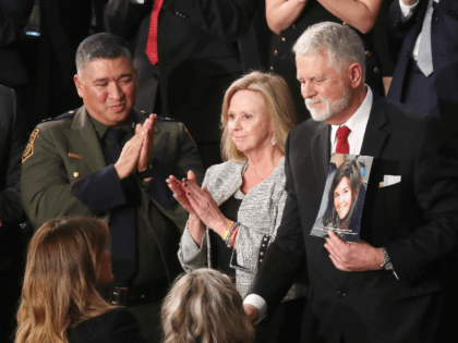 Carl Mueller (C) holds a photo of his daughter, Kayla, as his wife Marsha (L) looks on during the State of the Union address in the chamber of the U.S. House of Representatives on February 04, 2020 in Washington, DC. President Trump delivers his third State of the Union to …