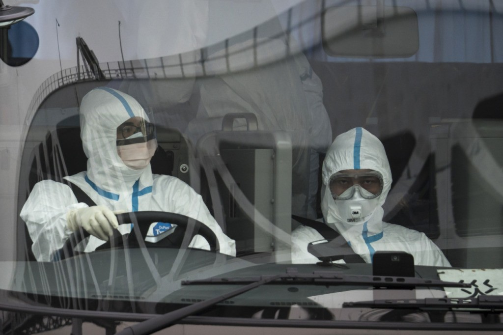 YOKOHAMA, JAPAN - FEBRUARY 20: Police officers wearing protective suites and masks are seen on a vehicle as they leave the quarantined Diamond Princess cruise ship, docked at the Daikoku Pier on February 20, 2020 in Yokohama, Japan. Passengers who have tested negative for the coronavirus (COVID-19) have been disembarking the cruise ship since Wednesday, as at least 634 passengers and crew onboard have tested positive for the coronavirus (COVID-19). Including cases onboard the ship, 718 people in Japan have now been diagnosed with COVID-19, making it the worst affected country outside of China. (Photo by Tomohiro Ohsumi/Getty Images)