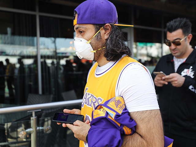 LOS ANGELES, CALIFORNIA - FEBRUARY 24: A fan wears a protective mask as people wait in line to attend the 'Celebration of Life for Kobe and Gianna Bryant' memorial service at Staples Center on February 24, 2020 in Los Angeles, California. Los Angeles Lakers NBA star Kobe Bryant, 41, and …