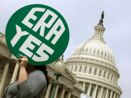 A woman hold up a sign as members of Congress and representatives of women's groups hold a rally to mark the 40th anniversary of congressional passage of the Equal Rights Amendment (ERA) outside the U.S. Capitol March 22, 2012 in Washington, DC. Rep. Carolyn Maloney (D-NY) and Sen. Robert Menendez …