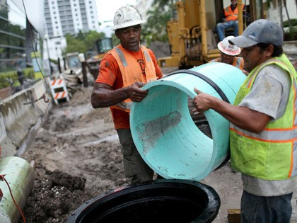MIAMI BEACH, FL - SEPTEMBER 25: Reluss Williams (L) and other construction workers install a drainage pipe that will be attached to a water pump station being built by the City of Miami Beach in the street on September 25, 2014 in Miami Beach, Florida. As climate change brings higher …
