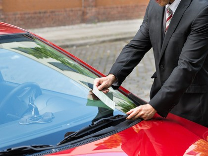 Close-up Of A Man Holding A Parking Ticket Placed On Car Windscreen