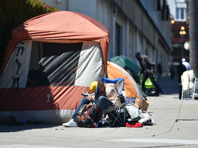 A homeless man sleeps in front of his tent along Van Ness Avenue in downtown San Francisco, California on June, 27, 2016. Homelessness is on the rise in the city irking residents and bringing the problem under a spotlight. (Photo by Josh Edelson / AFP) (Photo credit should read JOSH …