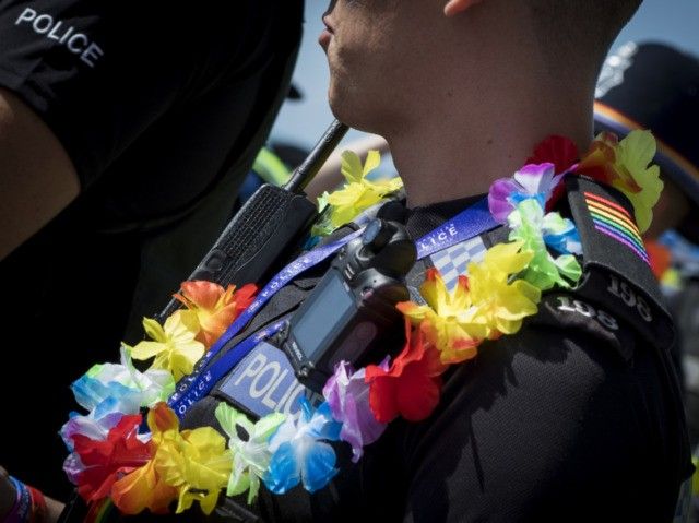 BRIGHTON, ENGLAND - AUGUST 05: A police officer wears a rainbow garland during the annual Brighton Pride Parade on August 5, 2017 in Brighton, England. (Photo by Tristan Fewings/Getty Images)