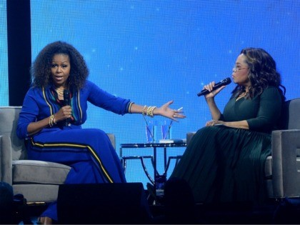 """Michelle Obama, left, and Oprah Winfrey speak onstage at """"Oprah's 2020 Vision: Your Life in Focus"""" tour at the Barclays Center on Saturday, Feb. 8, 2020, in New York. (Photo by Brad Barket/Invision/AP)"""