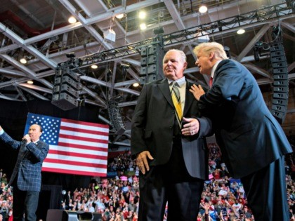 "US President Donald Trump speaks to radio talk show host Rush Limbaugh (C), while Lee Greenwood performs ""God Bless The USA"", at a Make America Great Again rally in Cape Girardeau, Missouri on November 5, 2018. (Photo by Jim WATSON / AFP) (Photo credit should read JIM WATSON/AFP via Getty …"