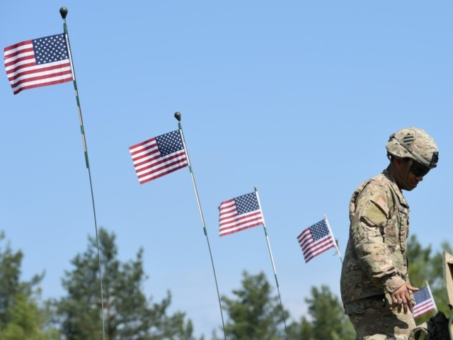 "A US soldier stands at a tank type ""M1A2 SEP"" which are decorated with US flags at a parking position at the training area in Grafenwoehr, near Eschenbach, southern Germany, on May 11, 2016, during the exercise ""Strong Europe Tank Challenge 2016"". The exercise is the first Europe-wide tank challenge …"