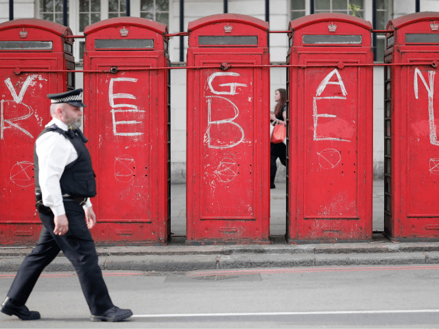 "A police officer walks past public telephone boxes daubed with the words ""vegan"" and ""rebel"" and the symbol of the Extinction Rebellion environmental protest group in London on April 22, 2019, on the eighth day of the group's protest calling for political change to combat climate change. - Climate change …"