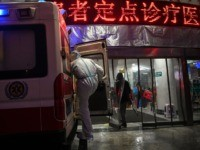 A medical staff member wearing protective clothing to help stop the spread of a deadly virus which began in the city, is seen on a ambulance at the Wuhan Red Cross Hospital in Wuhan on January 25, 2020. - The Chinese army deployed medical specialists on January 25 to the …
