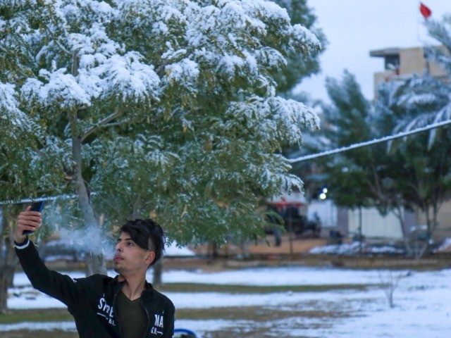 An Iraqi youth poses for a selfie in the snow in the holy Shiite city of Karbala on February 11, 2020. - Iraq's capital Baghdad woke up covered in a thin layer of fresh snow, an extremely rare phenomenon for one of the world's hottest countries. Snow also covered the …