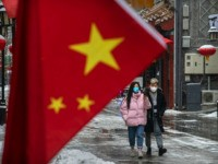 BEIJING, CHINA - FEBRUARY 05: A Chinese couple wear protective masks as they walk during a snowfall in an empty and shuttered commercial street on February 5, 2020 in Beijing, China. China's stock markets tumbled in trading on Monday, the first day back after an extended Lunar New Year holiday …