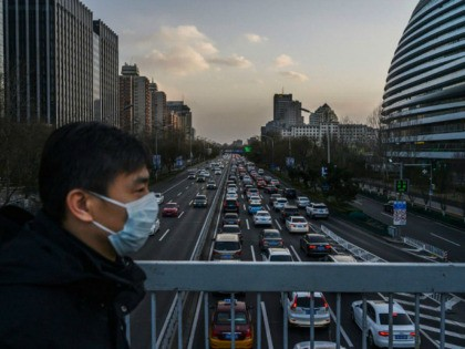 BEIJING, CHINA - FEBRUARY 21: A Chinese man wears a protective mask as he crosses a footbridge over the 2nd Ring Road during a busier rush hour than in the last weeks on February 21, 2020 in Beijing, China. The number of cases of the deadly new coronavirus COVID-19 being …