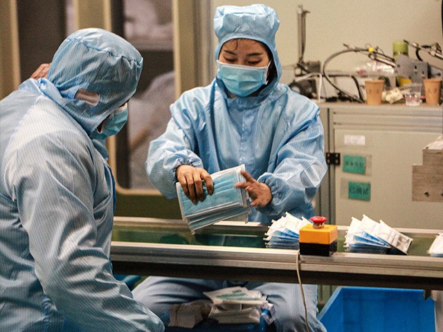 TOPSHOT - This photo taken on January 26, 2020 shows workers producing facemasks at a factory in Yangzhou in China's eastern Jiangsu province, to support the supply of medical materials during a deadly virus outbreak which began in Wuhan. - At least 81 people have died since the new strain …