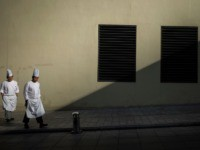 Chefs walk along a sidewalk in Beijing on January 14, 2020. - China's trade surplus with the United States narrowed last year as the world's two biggest economies exchanged punitive tariffs in a bruising trade war, official data showed Tuesday. (Photo by NOEL CELIS / AFP) (Photo by NOEL CELIS/AFP …