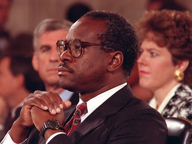 U.S. Supreme Court Justice nominee Judge Clarence Thomas is shown during his testimony before the Senate Judiciary Committee on Capitol Hill in Washington, D.C., Oct. 11, 1991. Thomas denies the charges of sexual harassment brought against him. His wife, Virginia, sits behind him. (AP Photo/Greg Gibson)