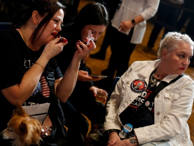 DES MOINES, IA - FEBRUARY 03: A woman with her dog applies lipstick as she attends Democratic presidential candidate former Vice President Joe Biden's Iowa caucus night event at Drake University on February 3, 2020 in Des Moines, Iowa. Iowa is the first contest in the 2020 presidential nominating process …