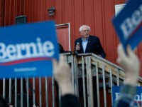 Democratic presidential candidate Sen. Bernie Sanders, I-Vt., accompanied by his wife Jane O'Meara Sanders, right, speaks to an overflow crowd at a Super Bowl watch party campaign event, Sunday, Feb. 2, 2020, in Des Moines, Iowa. (AP Photo/John Locher)