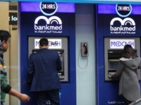 A Lebanese men withdraw money from a ATM in the capital Beirut on December 30, 2019 as the country imposes restrictions on dollar withdrawals and transfers abroad in an attempt to conserve dwindling foreign currency reserves. - Since September, banks have restricted the number of dollars that can be withdrawn …