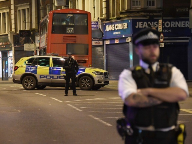A police officer stands guard near the scene after a stabbing incident in Streatham London, England, Sunday, Feb. 2, 2020. London police officers shot and killed a suspect after at least two people were stabbed Sunday in what authorities are investigating as a terror attack. (AP Photo/Alberto Pezzali)