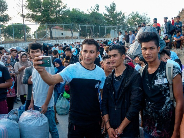 Refugees and migrants take selfie outside the Moria hotspot on the island of Lesbos, prior to their transfer to the island port and then to the country's mainland on October 6, 2019. - Hundreds of refugees and migrants will be relocated in camps in northern Greece from the overcrowded Moria …