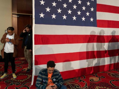 Young supporters check their phones as they attend the Caucus Night Celebration event for Democratic presidential candidate Vermont Senator Bernie Sanders in Des Moines, Iowa, on February 3, 2020. (Photo by kerem yucel / AFP) (Photo by KEREM YUCEL/AFP via Getty Images)