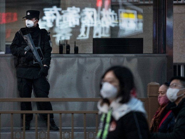 BEIJING, CHINA - JANUARY 21: A Chinese police officer on regular security duty wears a mask as he guards outside Beijing Railway station as masked travellers make their way to trains during the annual Spring Festival on January 21, 2020 in Beijing, China. The number of cases of a deadly …
