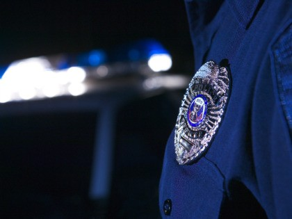Close-up of an officer's badge with the police lights on the car flashing in the background - stock photo
