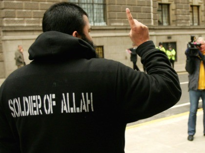 LONDON - FEBRUARY 07: A supporter of the controversial Muslim cleric Abu Hamza al-Masri is filmed by a British police officer as he protests outside of the Old Bailey criminal court on February 7, 2006 in London, England. Hamza has been found guilty of inciting murder and race hate and …