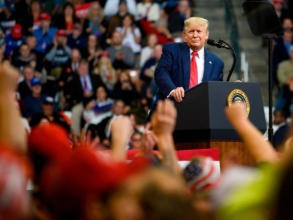 """TOPSHOT - US President Donald Trump looks at his supporters after reading words from Al Wilson's song """"The Snake"""" during a rally in Manchester, New Hampshire on February 10, 2020. (Photo by JIM WATSON / AFP) (Photo by JIM WATSON/AFP via Getty Images)"""
