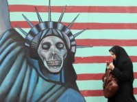 "An Iranian woman walks past an anti-US mural painted on the wall of the former US embassy in Tehran on November 19, 2011. The United States said Iran was now locked in ""unprecedented"" isolation after UN bodies overwhelmingly condemned its nuclear programme and an alleged Tehran-planned terror plot. AFP PHOTO/ATTA …"