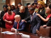 US President Donald Trump (C) stands in a prayer circle during a meeting with African-American leaders in the Cabinet Room of the White House in Washington, DC, on February 27, 2020. (Photo by Nicholas Kamm / AFP) (Photo by NICHOLAS KAMM/AFP via Getty Images)