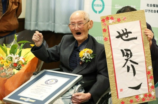 Japanese Chitetsu Watanabe, aged 112, poses next to the calligraphy reading in Japanese 'World Number One' after he was awarded as the world's oldest living male
