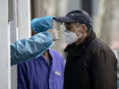 An elderly man wearing a face mask has his temperature checked before entering a community hospital in Shanghai