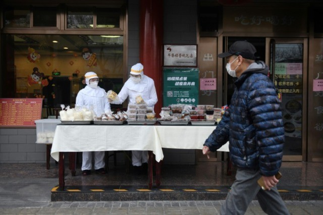 Restaurant workers wear protective clothing as they prepare food to sell on the street outside their restaurant in Beijing