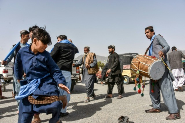 """Afghans dance as they celebrate the first day of a """"reduction in violence"""" agreement between the Taliban, US and Afghan forces in Kandahar"""