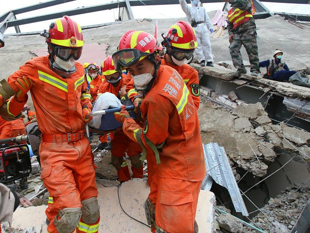A man (C) is rescued from the rubble of a collapsed hotel in Quanzhou, in China's eastern Fujian province on March 8, 2020. - At least four people were killed following the collapse of a hotel used as a coronavirus quarantine facility in eastern China, the Ministry of Emergency Management …