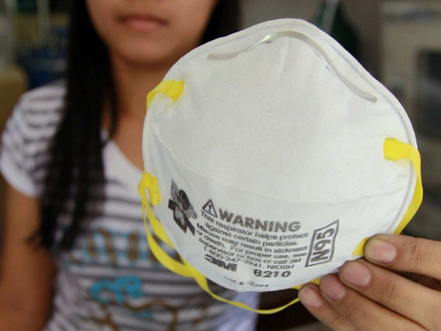 In a May 6, 2009 file photo a store attendantholds an N-95 mask over a box of disposable surgical masks in Manila, Philippines. Health workers caring for patients who have or may have swine flu should wear a special type of mask called an N95 respirator, not looser-fitting surgical masks, …