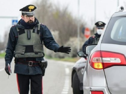 Italian police stop vehicles to check papers.