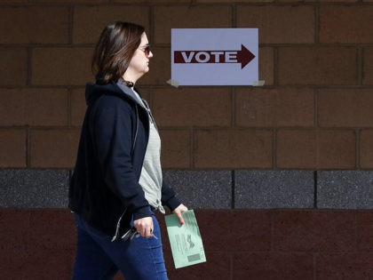 An Arizona voter delivers her mail-in ballot at a polling station for the Arizona presidential preference election Tuesday, March 17, 2020, in Phoenix. (AP Photo/Matt York)
